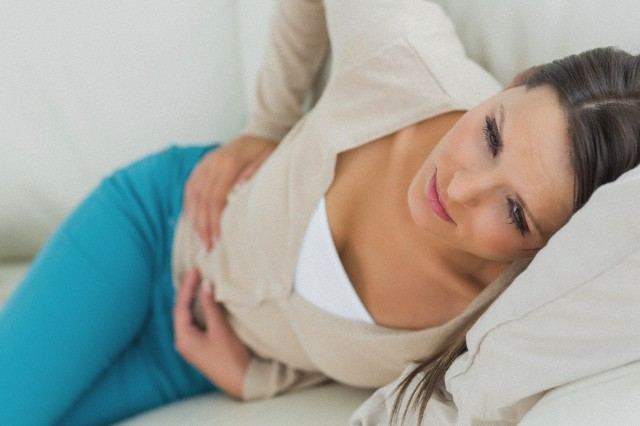 Woman lying on sofa looking sick